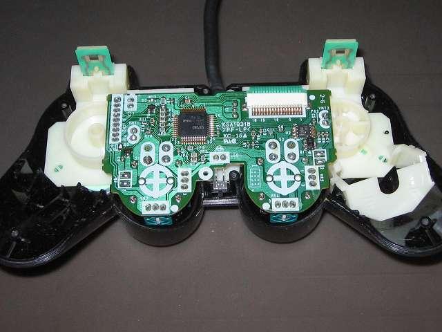 PS2 プレイステーション2 コントローラー DUALSHOCK 2 デュアルショック2 SCPH-10010 メンテナンス、組立作業 プラスチックボタン、ラバーパッドを取り付けたコントローラー本体上部プラスチックカバーに基板を取り付ける。振動モーターのリード線切断のため画像には振動モーターが映っていないが、通常は振動モーターも基板と一緒にセットする