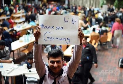 ドイツ西部ドルトムントで、鉄道駅に到着してバスを待ちながら「ありがとう、ドイツ」と書かれた紙を掲げる移民(2015年9月6日)〔AFPBB News〕