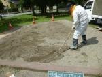 砂場表面をレーキで掻き集める